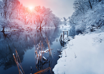 Beautiful winter in forest on the river at sunset. Winter landscape. Snowy branches on trees, beautiful river with reflection in water, sun and blue sky. Seasonal background. Frosty cold evening