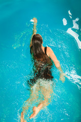 Woman floating resting in swimming pool water.
