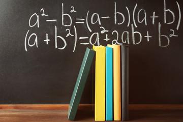Books on blackboard background