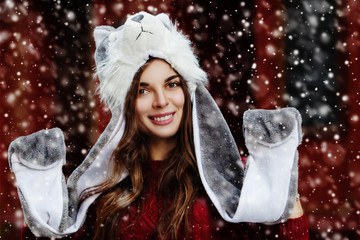 Outdoor close up portrait of young beautiful happy smiling girl, wearing stylish winter fur wolf hat. Model expressing joy and looking at camera. Christmas, New Year concept. Magic snowfall effect.