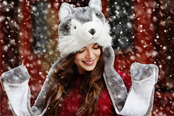 Outdoor close up portrait of young beautiful happy smiling girl, wearing stylish winter fur wolf hat. Model closed her eyes. Christmas, New Year, winter holidays concept. Magic snowfall effect.