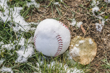 Baseball on grassy field covered in light dusting of snow