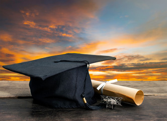 graduation cap, hat with degree paper on wood table, sunset sky