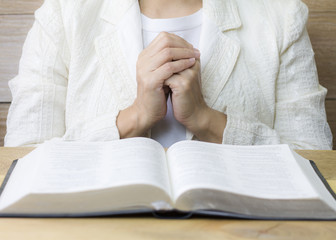 a woman praying   behind the holy bible  on wooden table