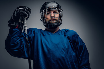 Bearded ice-hockey player in safety helmet holds the gaming stic