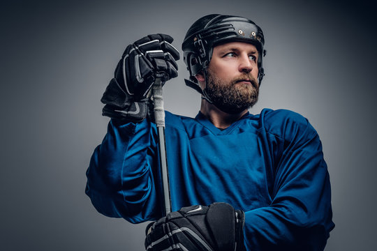 A bearded ice-hockey player in safety helmet holds the gaming st