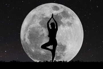 Silhouette young woman with good shape practicing yoga under full moon at night with stars Fotoväggar