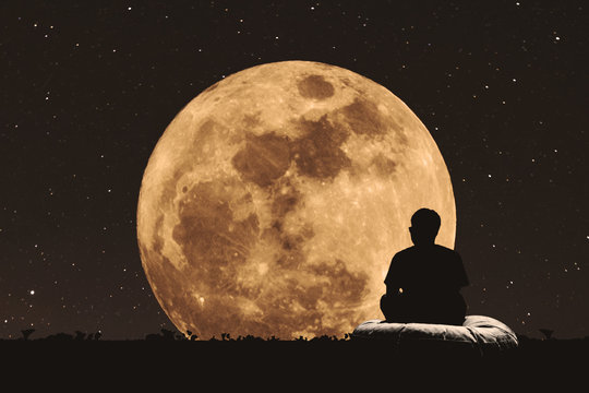 Silhouette a man sitting relaxing under full moon at night with stars on the sky