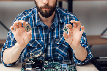 Engineer shows computer microchips. Electronic repair shop, laptop disassembling, technology fixing concept