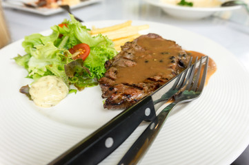 grilled pork steak served with crisp french fries and salad