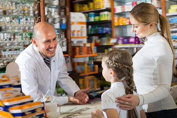 Adult male pharmacist helping customers