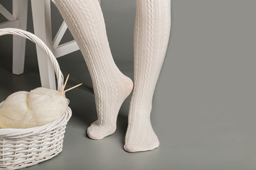 Female feet in white knitted tights near the basket with yarn an