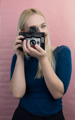 Girl taking photo on retro vintage hipster camera