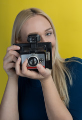 Girl taking photo on retro vintage hipster camera