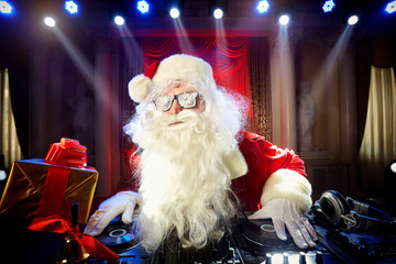 Dj Santa Claus at Christmas with glasses and snow mix on New Yea