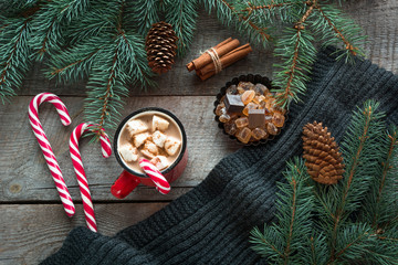 Mug hot coffee with milk, red candy cane on the wooden background with cone, branch of christmas tree and grey scarf. New Year. Holiday card. Rustic style. Top view and copy space.