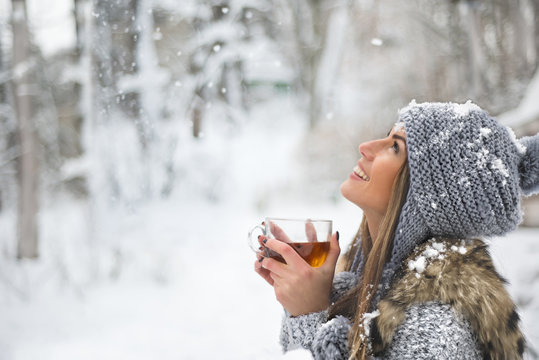 Girl enjoys the snow falls. Young woman in a knitted shape is drinking tea in the forest during a snowfall. Toned photo