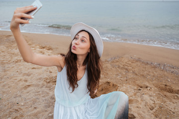 Funny woman taking selfie with cell phone on the beach