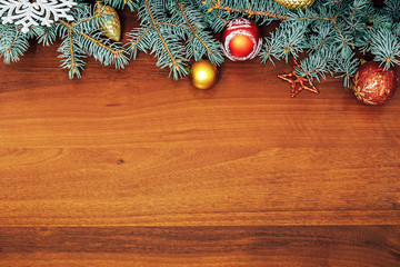 Christmas tree branches with Christmas toys on wooden background. Space for text