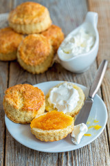 Scones with orange jam and whipped cream for breakfast.