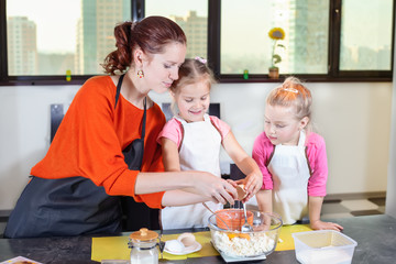 Two lovely children together with mother preparing a cake