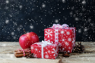 Christmas gifts with cinnamon and apple on dark background.