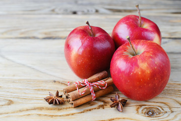 Some red apples with cinnamon on wood background.