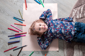 Child lying on the floor  paper looking at the camera near crayons. Little girl painting, drawing. Top view. Creativity concept.