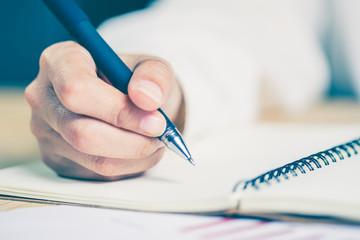 Business women hands working writing notebook on wooden desk, li