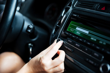 Woman hand turning button of radio in car