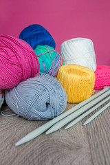 Knitting. Group of yarn and needles on grey wooden table  pink background. Handmade. Close up.
