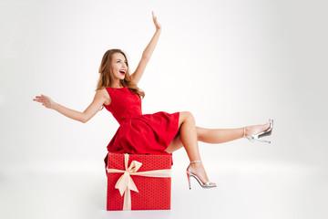 Woman in red dress having fun on big gift box