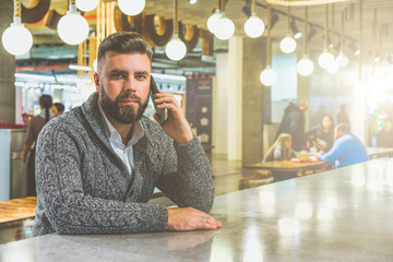 Front view of a young bearded businessman, dressed in a gray cardigan, sitting at a table with a glossy surface in cafe, talking on mobile phone. A man uses the gadget.