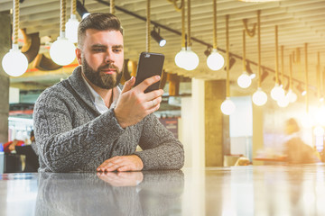 Young bearded businessman,dressed in gray cardigan,sitting at table in cafe and use smartphone. Man holding smartphone and looking at its screen. Man using gadget. Guy browsing internet on smartphone.