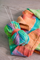 Knitting. Knitted sweater. Multicolor ball of yarn with needles near the handmade products. Close up.