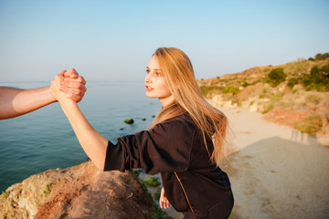 Man hand helping woman to climb a hill at seaside