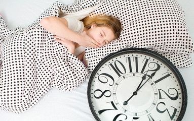 Beautiful sleeping girl resting in bed with alarm clock , The sleeping teenager
