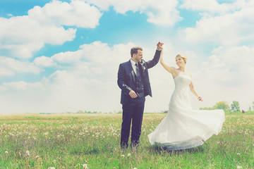 Brautpaar tanzt auf einer Wiese