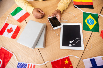 Man using cell phone, tablet, books and flags of countries