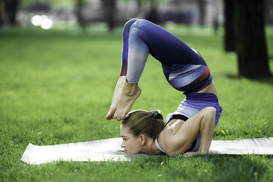 Girl practicing yoga in the park on the green grass