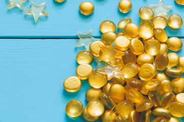 Close up image of yellow marbles on blue wooden background