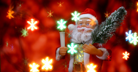 Santa Claus toy brings Christmas tree at glow red bokeh background and blurred lights snowflakes foreground. Big Copyspace concept New Year`s market banner, poster.