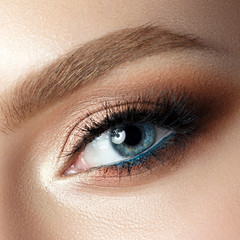 Close up view of blue woman eye with beautiful makeup