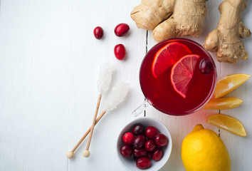 Fresh cranberry juice with lemon, berry, ginger and sugar on a light background. Top view. Space for text. Selective focus.