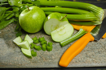 Green vegetables and fruits -  celery shoots and  apples, dietary concept