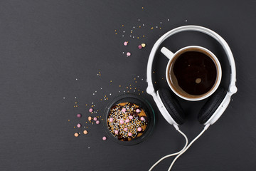 Cup of coffee, chocolate muffin and headphones