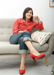 young woman with jeans sitting in the sofa