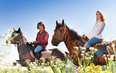 Portrait of young couple horseback riding