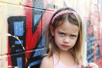 Poor child leaning up against a graffiti wall in the city looking sad.