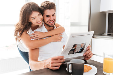 Couple hugging and reading newspaper on the kitchen